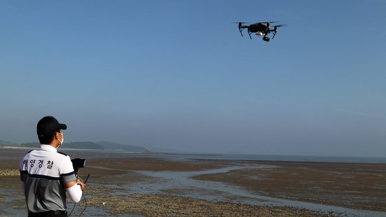 지난 20일 보령해경 경찰관이 충남 서천군의 한 갯벌에서 드론을 이용해 체험객들에게 바닷물 만조시간을 전달하고 있다. [사진 보령해경]
