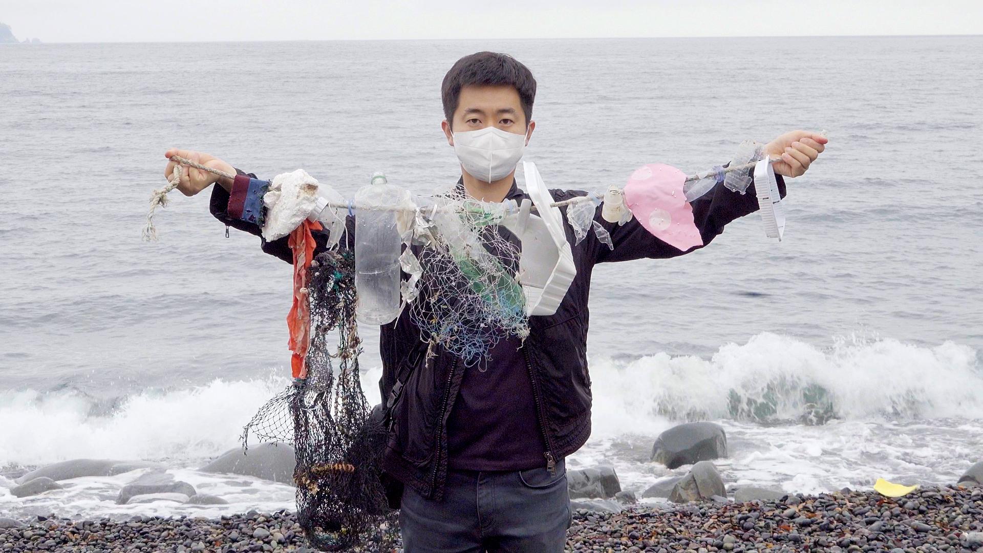 기자가 거제도 해변에 밀려온 플라스틱 쓰레기들을 들고 있다. 왕준열PD