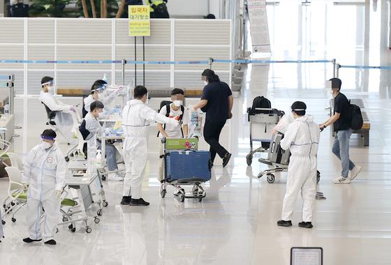 인천국제공항 제2터미널 입국장에서 방역관계자들이 해외 입국자들을 안내하고 있다. 연합뉴스