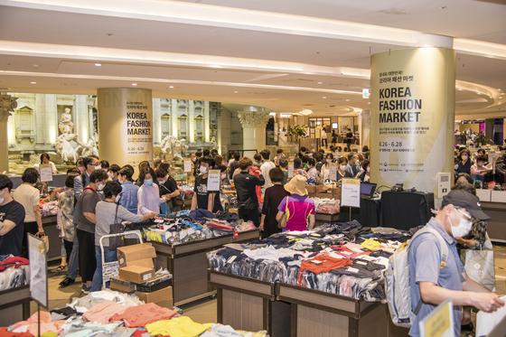 지난해 6월 열린 '코리아패션마켓' 첫 날 서울 중구 롯데백화점을 찾은 사람들이 물건을 둘러보고 있다. 사진 한국패션산업협회