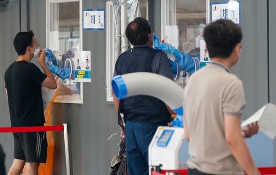 신종 코로나바이러스 감염증(코로나19) 신규 확진자가 645명 발생한 23일 서울역 광장에 마련된 중구 임시선별검사소에서 의료진이 검체채취를 하고 있다. 뉴스1