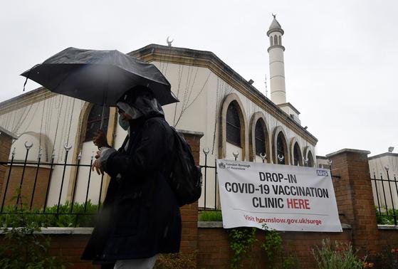 한 시민이 영국 런던내 코로나19 예방접종 클리닉 앞을 지나고 있다. 로이터=연합뉴스