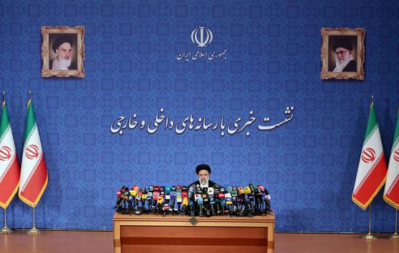 21일 이란 수도 테헤란에서 열린 에브라힘 라이사 대통령 당선인의 내외신 기자회견 장면. 뒷쪽 벽면 위에는 이란 국장과 이란 이슬람 공화국이란 글자가, 아래에는 내외신 기자회견이라는 글이 각각 적혀 있다. 벽면 위에는 초대 최고지도자인 루홀라 호메니이(왼쪽)과 와 현재 최고지도자인 알리 하메네이의 초상이 걸려 있다. 애랫쪽 좌우에는 이란 국기가 세워져 있다. UPI=연합뉴스