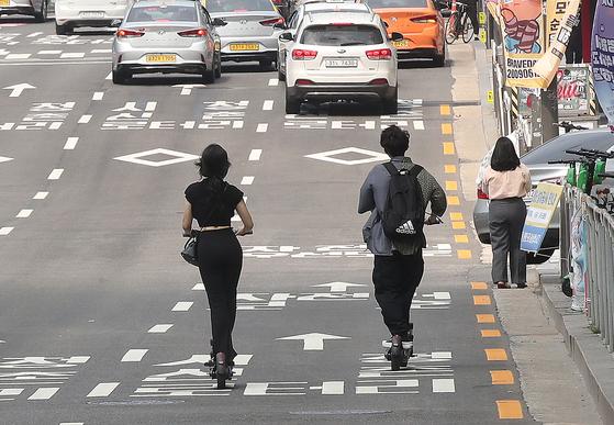 개인형 이동장치(PM) 운전자의 안전 강화를 위한 도로교통법 개정안이 시행된 6월13일 오후 서울 시내에서 한 커플이 헬멧을 미착용하고 도로를 달리고 있다. 우상조 기자