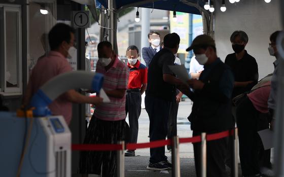 국내 신종 코로나바이러스감염증(코로나19) 신규 확진자 수가 600명대 중반을 기록한 23일 오전 서울역 광장에 마련된 임시선별검사소를 찾은 시민들이 검체 검사를 기다리고 있다.   연합뉴스