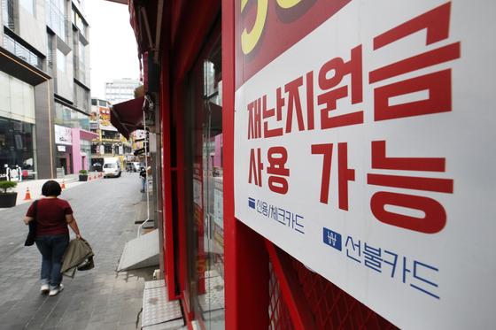 지난 22일 서울 명동의 한 점포에 재난지원금을 사용할 수 있다는 안내문이 붙어 있다. [뉴스1]