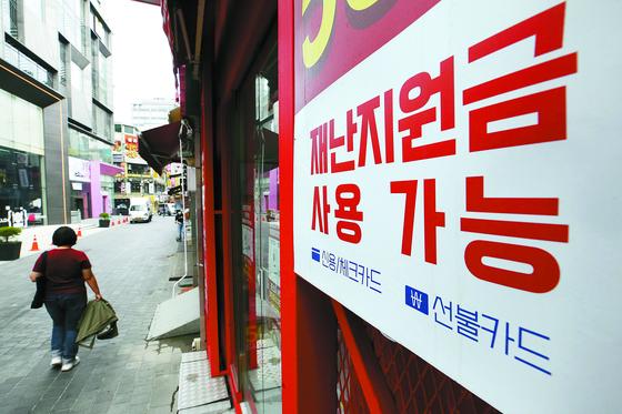 지난 22일 오전 서울 중구 명동의 한 점포에 재난지원금 사용 가능함을 알리는 안내문이 부착돼 있다. 뉴스1