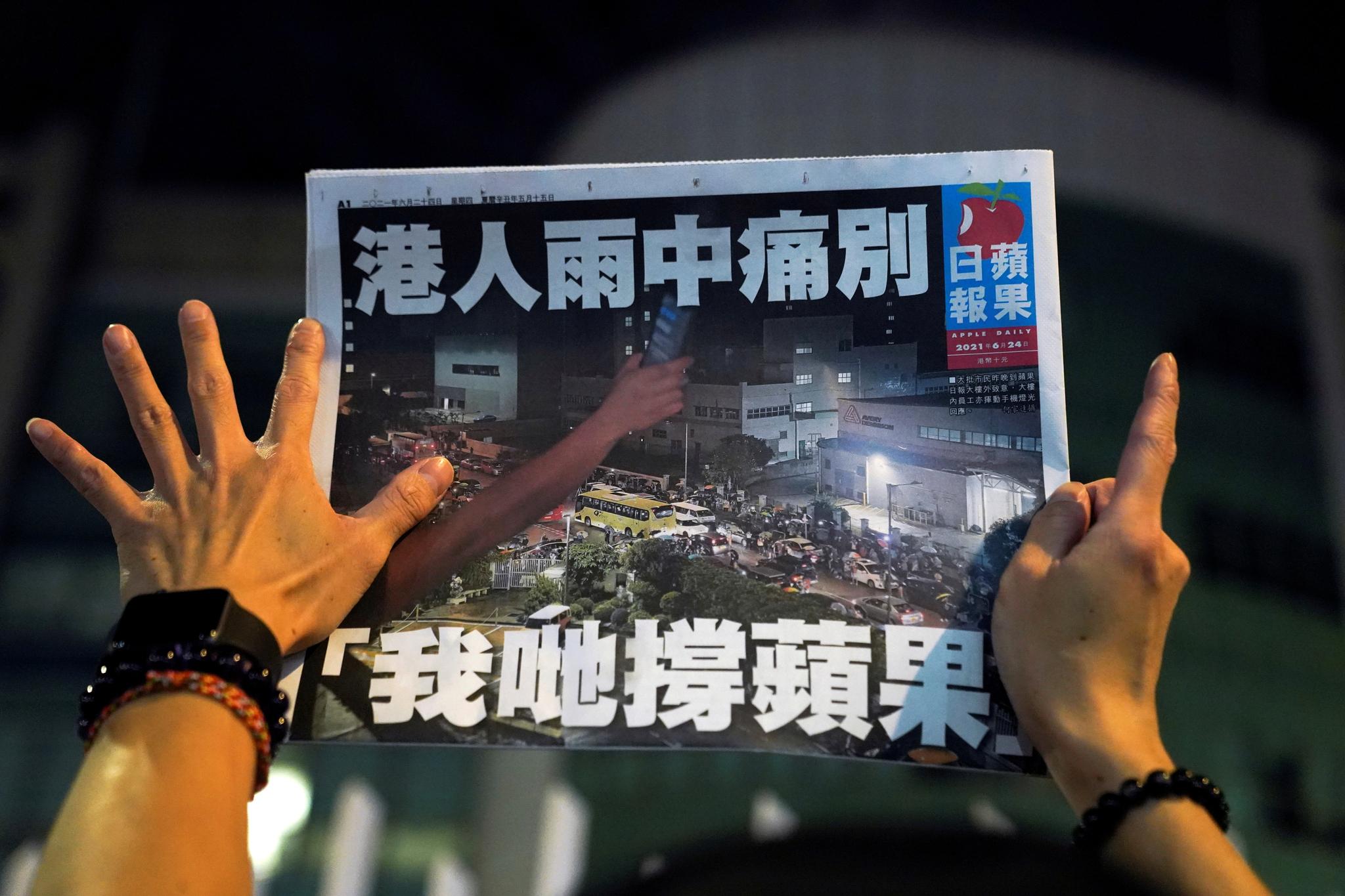 한 홍콩 시민이 24일 빈과일보 마지막 발행본을 펼쳐서 읽고 있다. 로이터=연합뉴스〉