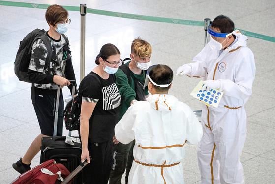 지난 23일 인천국제공항 제1여객터미널 입국장에서 방역당국 관계자들이 입국객들을 안내하고 있다. 뉴스1