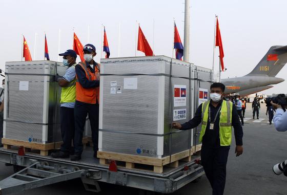 지난 2월 7일 캄보디아 프놈펜 국제공항에 중국산 백신 시노팜 60만 회분이 들어오고 있다. 백신 보관 박스 위에는 중국과 캄보디아의 국기가 꽂혀있다. [AP=연합뉴스]