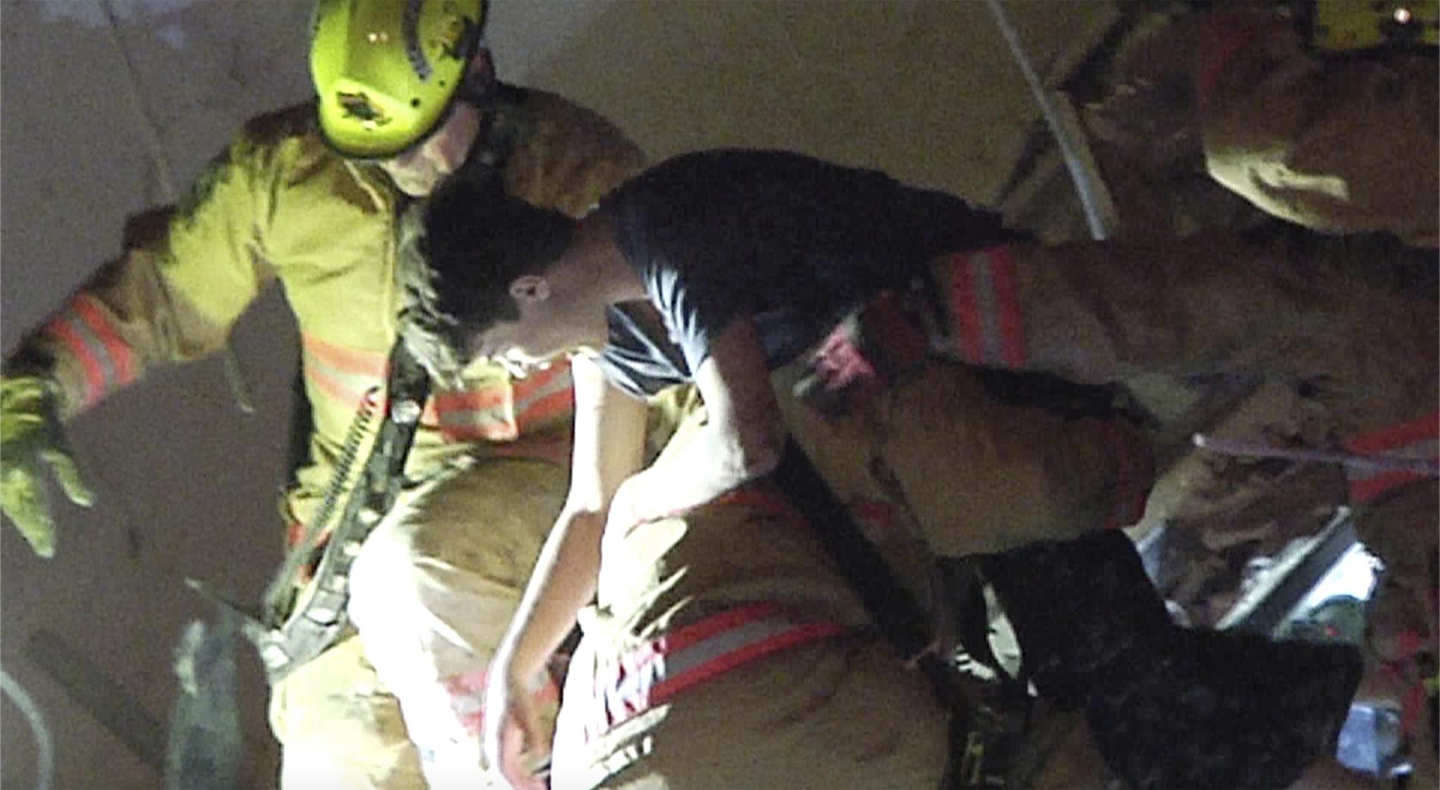 24일(현지시각) 미국 마이애미주 서퍼사이드 아파트 붕괴사고 현장에서 구조대원들이 잔해 속에서 생존자를 구하고 있다. AP=연합뉴스