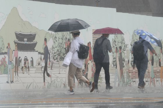 지난 23일 오후 서울 광화문광장에서 갑작스런 소나기에 우산을 쓴 시민들이 걸음을 재촉하고 있다. 연합뉴스