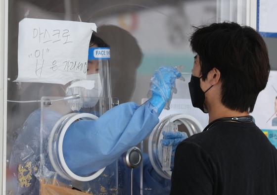 25일 오후 서울 중구 서울역 광장에 마련된 중구임시선별검사소에서 한 시민이 신종 코로나바이러스 감염증(코로나19) 선별검사를 받고 있다. 연합뉴스