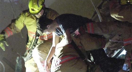 건물 잔해 속에서 24일 소방관이 한 소년을 구조하고 있다. AP