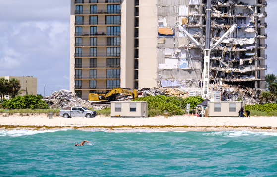 A man swims in the sea in front of the site of an apartment collapse on the beach in Miami, Florida, USA. [로이터=연합뉴스]
