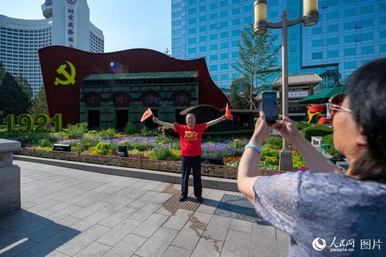 중국 베이징의 시민들이 중공 창당 100주년을 축하하기 위해 조성된 화단을 배경으로 사진을 찍고 있다. [중국인민망 캡처]