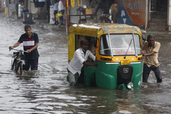 아시아 지역에 여름 몬순이 닥친 가운데 지난 22일 인도 아메다바드 주민이 폭우에 침수된 자동인력거(오토릭샤)를 밀고 있다. [AP=연합뉴스]