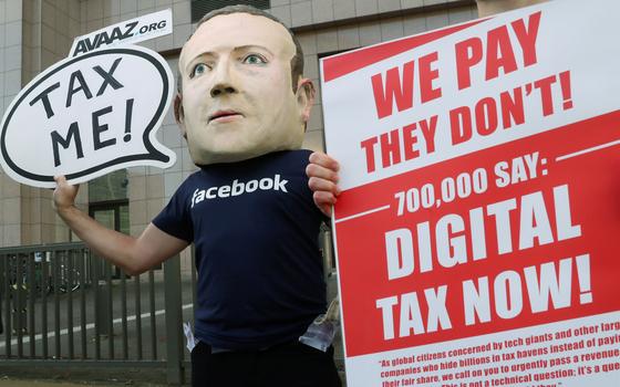 한 시민운동가가 지난 2018년 이른바 '구글세' 도입을 주장하며 마크 저커버그 페이스북 최고경영자(CEO) 마스크와 복장을 입고 브뤼셀 유럽연합 본부 앞에서 1인 시위를 하는 모습. [로이터=연합뉴스]