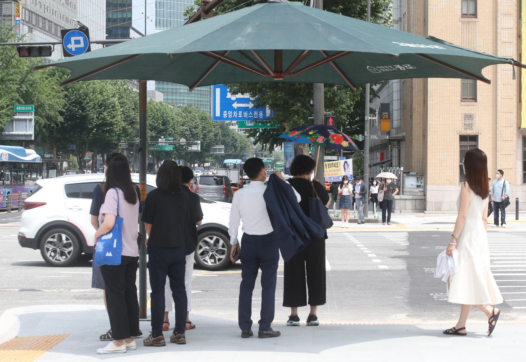 6일 서울 광화문 세종대로에서 시민들이 햇볕을 피해 서 있다. 중앙포토