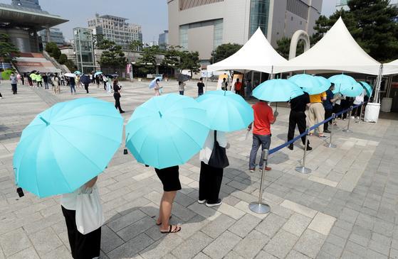 수도권에 사회적 거리두기 4단계가 시행된 12일 오후 인천시 남동구 구월동 한 선별검사소에서 시민들이 양산을 들고 검사를 기다리고 있다. 연합뉴스