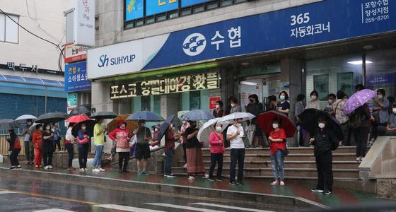 지난 7일 오전 경북 포항시 북구 수협장성지점 앞에서 시민들이 포항사랑상품권을 구입하기 위해 장맛비를 맞으며 줄을 서서 기다리고 있다. 뉴스1