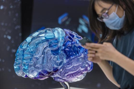 지난 5월 중국 상하이에서 열린 국제의료장비전시회에서 한 관람객이 인간 뇌 모형이 전시된 곳을 지나가고 있다. [EPA=연합뉴스]