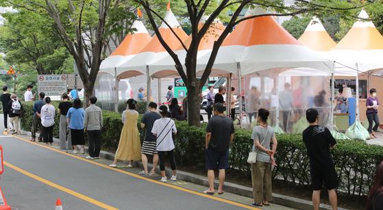 12일 연제구보건소 선별진료소를 찾은 시민들이 진단검사를 받기 위해 줄서서 자신의 차례를 기다리고 있다. 송봉근 기자