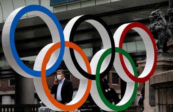 12일 마스크를 쓴 시민이 일본 도쿄 시내의 올림픽 조형물을 지나고 있다. [로이터=연합뉴스]