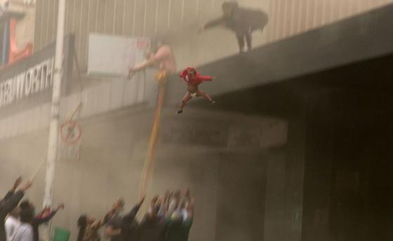남아공 더반의 한 주상복합 건물. 1층 상점에 불이 나자 건물 윗층에 있던 아기 엄마가 아기를 밑에 모인 사람들의 품에 던지고 있다. [BBC 캡처]
