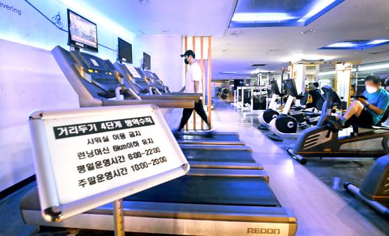거리두기 4단계 첫날인 지난 12일 서울 은평구 연신내 한 헬스장에서 회원들이 런닝머신 등 기구를 이용하고 있다. 뉴시스