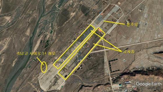 북중 국경 군사공항인 의주비행장. 지난 3월 촬영한 사진으로 활주로 양옆이 공사장으로 변해 있다. 기존에 격납고로 사용하던 곳엔 철로가 들어섰다. [구글어스 캡처]