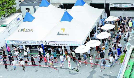 지난 13일 오전 서울 강남구 보건소 선별진료소에서 시민들이 신종 코로나바이러스 감염증(코로나19) 선별 검사를 받기 위해 대기하고 있다.   연합뉴스