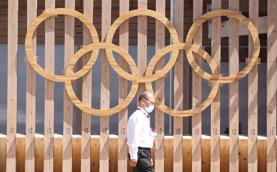 2020 도쿄올림픽 개막을 일주일 앞둔 16일 일본 도쿄 하루미 지역 올림픽선수촌 입구에서 관계자가 오륜기 조형물 앞을 지나고 있다. 도쿄=올림픽공동취재단