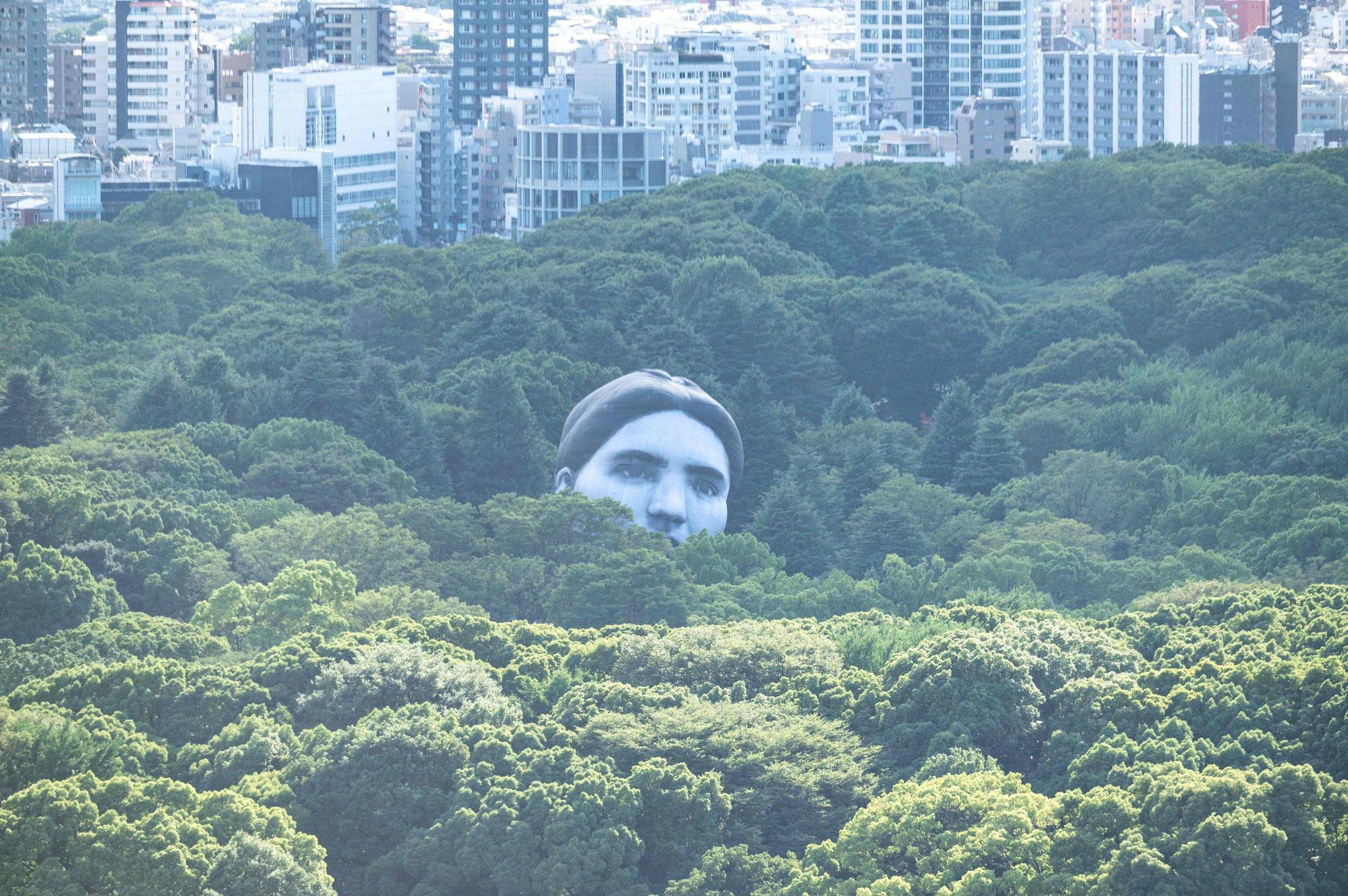 '꿈이 현실에서 이루어진다'는 의미의 공공미술 열기구 '마사유메'(正夢)가 16일 일본 도쿄 요요기공원 나무숲 사이로 떠오르고 있다. AFP=연합뉴스