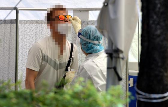 신종 코로나바이러스 감염증(코로나19) 신규 확진자가 휴일 역대 최다인 1454명 발생한 18일 대전의 한 코로나19 선별진료소에서 의료진이 방문한 시민을 신중히 검사하고 있다. 프리랜서 김성태