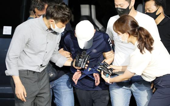 지인과 공모해 옛 연인의 중학생 아들을 살해한 혐의를 받고 있는 40대 남성 A씨가 도주 하루 만인 19일 오후 8시57분쯤 제주동부경찰서로 호송되고 있다. 뉴스1