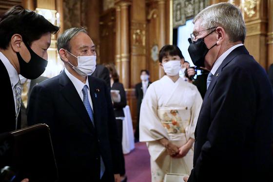 토마스 바흐 국제올림픽위원회(IOC) 위원장이 지난 18일 도쿄 아카사카 영빈관에서 열린 일본 정부 주최 환영 행사에 참석해 스가 요시히데 총리와 환담하고 있다. AFP=연합뉴스