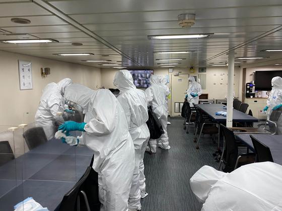 코로나19 집단감염이 발생한 청해부대 34진을 국내로 이송하기 위해 출국한 특수임무단이 19일(현지시간) 아프리카 해역에서 문무대왕함에 승선해 방역작업을 하고 있다. 뉴스1