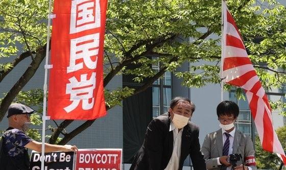 대한민국 올림픽 선수단 본진이 도쿄로 입성하는 19일 도쿄올림픽 대한민국 올림픽 선수촌 앞에서 일본 극우단체 회원들이 욱일기를 들고 시위를 하고 있다. 뉴스1
