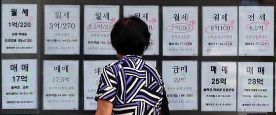 서울 시내 한 부동산 공인중개사 사무소에 아파트 매매·전세 매물 전단이 붙어있다. [뉴스1]   20일 서울시내 한 부동산 공인중개사 사무소에 매물 전단이 붙어있다. 정부가 지난 19일 전세를 월세로 전환할 때 적용하는 '전월세 전환율'을 기존 4%에서 2.5%로 하향조정하기로 발표했다. 국토교통부는 법무부와 함께 새로운 전월전환율을 세입자의 집주인 임대차 정보열람권과 함께 이달 입법예고할 방침이다. 이 경우 시행은 10월이 유력시된다. 2020.8.20. [뉴스1]