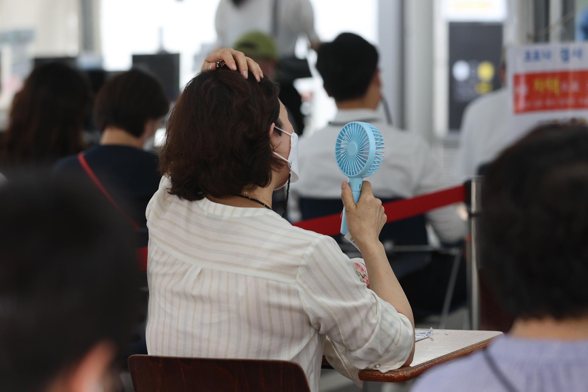 폭염이 계속되는 가운데 20일 오후 서울 강남구보건소 선별진료소에서 시민이 휴대용 선풍기로 더위를 식히고 있다. 연합뉴스