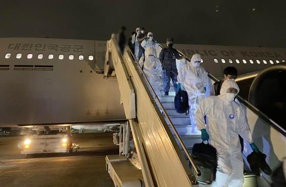 신종 코로나바이러스 감염증(코로나19)에 집단감염된 청해부대 34진 전원을 수송하기 위해 현지에 파견한 특수임무단이 19일 공군 다목적 수송기에서 내리고 있다. [연합뉴스]