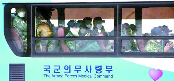 """버스에 탑승한 청해부대 34진 문무대왕함 장병들이 20일 오후 성남 서울공항을 빠져나오고 있다. 국방부는 """"장병들은 군 병원 두 곳, 군과 민간의 생활치료센터 각각 한 곳으로 이동할 예정이며, 특히 중등도 증상을 보이는 3명을 포함한 14명은 의료기관으로 이송될 계획""""이라고 밝혔다. 또 """"전원 유전자증폭(PCR) 검사 진행 후 '음성'으로 확인될 경우 군내 격리시설로 이동하게 된다""""고 덧붙였다. [뉴스1]"""