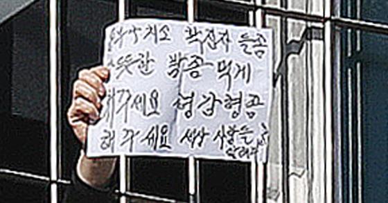 지난 1월 6일 오후 서울 송파구 동부구치소에서 한 재소자가 신종 코로나바이러스 감염증(코로나19) 확진 재소자들에게 따뜻한 식사 제공과 감형을 촉구하는 글을 창살 너머로 꺼내 보이고 있다. 뉴스1