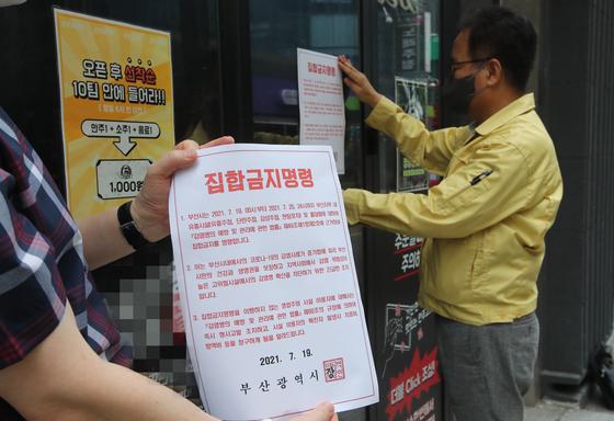 19일 부산진구청 직원들이 서면일대 유흥업소 입구에 집합금지 행정명령 안내문을 부착하고 있다. 집합금지 행정명령은 25일까지 계속된다. 송봉근 기자