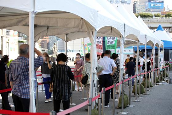 21일 오전 서울역 광장에 마련된 중구임시선별검사소에서 시민들이 신종 코로나바이러스 감염증(코로나19) 선별검사를 받기 위해 줄을 서 있다. 연합뉴스