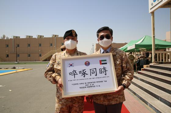"""지난 3월 24일 한-UAE 국방장관 회담을 위해 UAE를 방문한 서욱 국방부 장관(오른쪽)이 파병 10주년을 맞은 아크부대를 방문, 부대장인 김명응 중령에게 부대표창을 수여한 뒤 기념촬영을 하고 있다. 액자에는 줄탁동시(啐啄同時)라는 사자성어와 함께 """"큰일을 이루어 내기 위해서는 안과 밖, 모든 사람이 한마음으로 노력해야 한다""""는 내용이 적혀 있다. [연합뉴스]"""