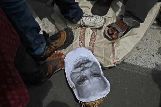 지난달 11일 나렌드라 모디 인도 총리에 반대하는 집회가 열리고 있다. 시위대가 그의 이미지를 짓밟고 있다. [AFP=연합뉴스]