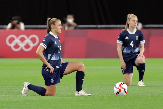 21일 일본 삿포로 돔에서 열린 도쿄 올림픽 여자축구 E조 영국-칠레 1차전에서 영국의 조지아 스탠웨이(완쪽)와 키이라 월시가 선수가 인종차별에 항의하기 위한 무릎 꿇기 세리머니를 하고 있다. [AFP=연합뉴스]