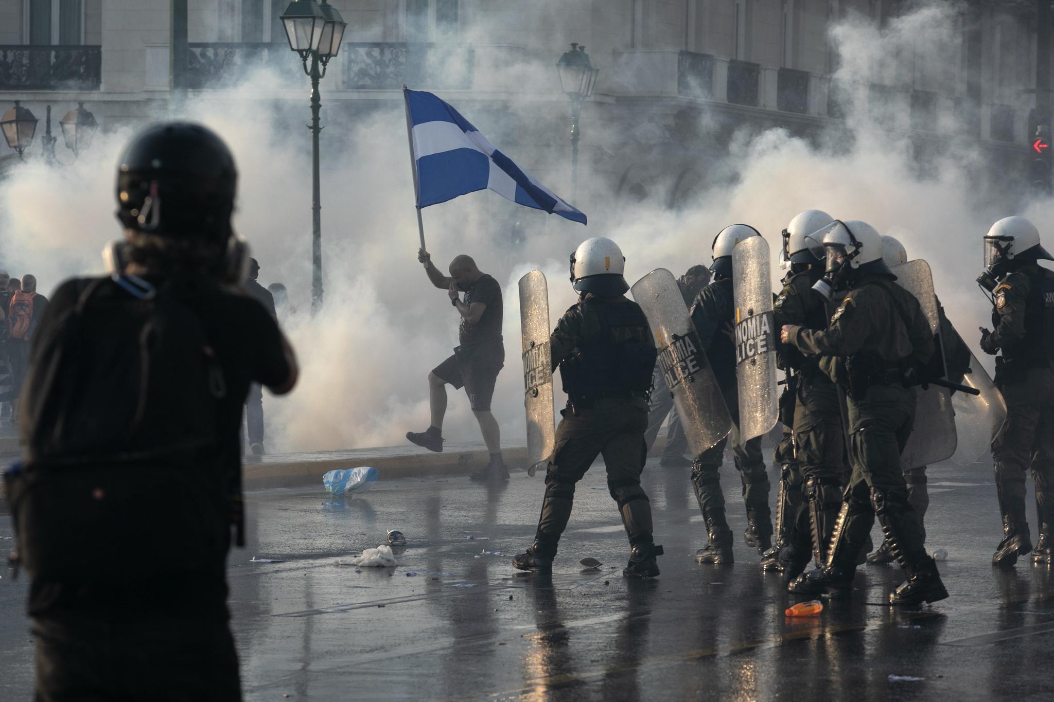 그리스 경찰이 21일(현지시각) 수도 아테네 도심 국회의사당 광장에서 코로나 백신 반대 시위대를 향해 최루탄을 쏘고 있다. 이날 수천명의 그리스 시민이 정부의 백신 접종 확대 정책에 반대하는 시위에 참여했다. 현재 그리스의 백신 접종 완료율은 약 45% 수준이다. AP=연합뉴스